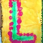 Initiale au pastel entourée d'empreintes de bouchon à la peinture